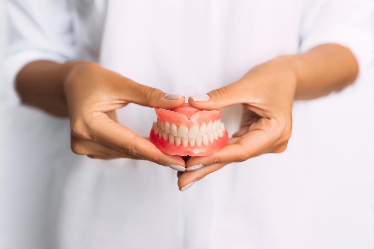 Frau hält Zahnprothesen